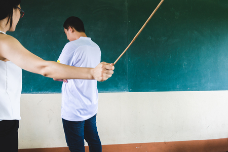 Students being physically punished by teacher with small wooden stick 免版税图像