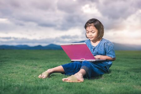 Asian children in local dress are using laptop for education and communication at countryside of Thailand. Stock Photo