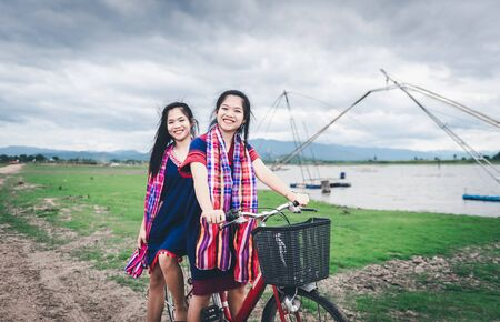Beautiful Asian girls enjoy travel at countryside of Thailand by riding on bicycle Reklamní fotografie