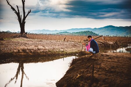 Water crisis concept, Hopeless and lonely farmer sit on cracked earth near drying water.