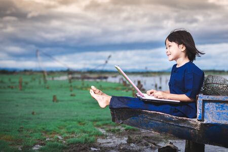 Asian children in local dress are using laptop for education and communication at countryside of Thailand.