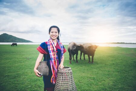 Beautiful Asian girl holding fish trap and basket, prepare to catch fish walking in field near lake at countryside of Thailand