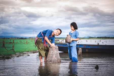 Children catching fish and have fun in the canal. Life style of children in countryside of Thailand. Banco de Imagens