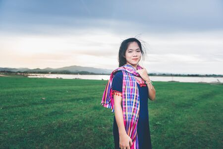 Portrait of beautiful Asian girl with local dress, standing in the mist of fieldt at countryside of Thailand