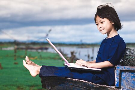 Asian children in local dress are using laptop for education and communication at countryside of Thailand. Banco de Imagens