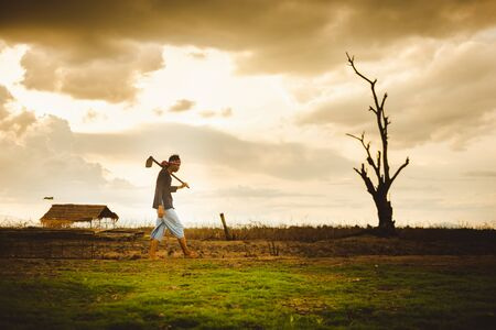 Hopeless and lonely Farmer carrying hoe and walking through his dry field at sunset. Global warming crisis,  Economic crisis concept. Banco de Imagens