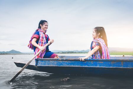Beautiful Asian girls on fishing boat in lake to catch fish at countryside of Thailand
