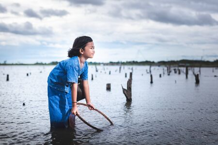 Children have fun fishing in lakel. Life style of children in countryside of Thailand.