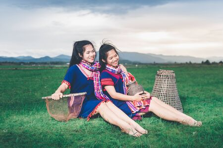 Beautiful Asian girl holding fish trap and basket, resting aftero catch fish, sitting on ground in field near lake at countryside of Thailand