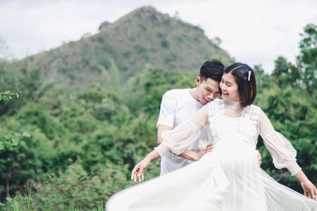 Portrait of Asian husband hug and kissing his pregnant wife with natural background. Asian Married couple and family concept.