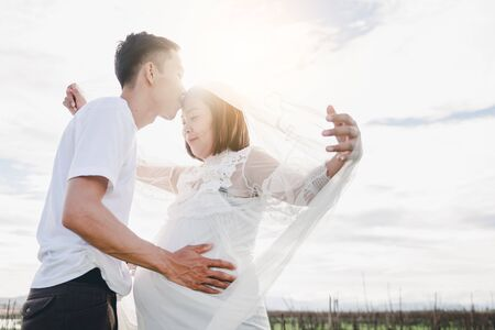 Asian husband kissing his pregnant wife with his eyes closed in mountain. Asian Married couple and family concept. Stok Fotoğraf