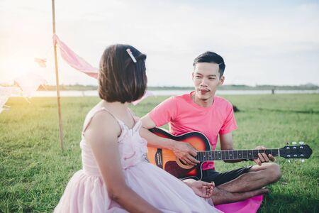 Marido asiático tocando la guitarra y disfrutar con su esposa embarazada al aire libre Pareja casada asiática y concepto de familia.