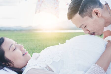 Asian husband kissing his pregnant wife with his eyes closed. Asian Married couple and family concept. Stok Fotoğraf
