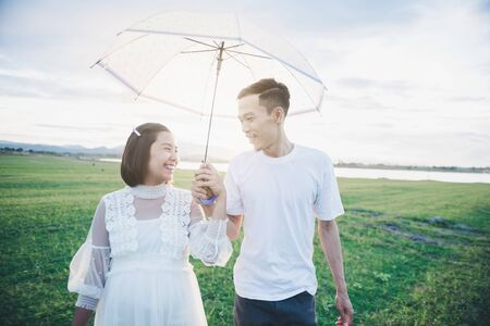Pregnant wife with her husband enjoy walking with umbrella outdoor with sunset in morning