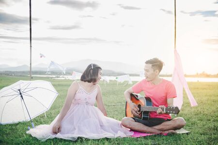 Asian husband playing guitar and enjoy with his pregnant wife outdoor Asian Married couple and family concept.