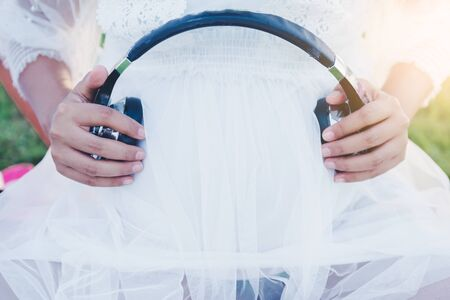 Pregnant woman put earphone on her belly for unborn baby to listen to music