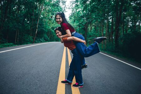 Cute Asian young girl on a piggy back ride with her sister, natural travel concept