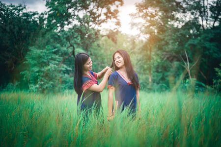 Portrait of young girls enjoy playing in the mist of foresst outdoor at countryside of Thailand