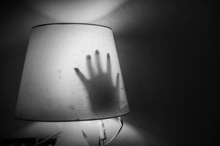 Horror shoot, hand of woman out from the lamp in white tone