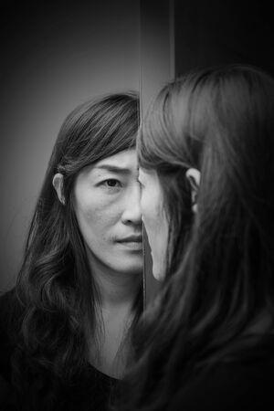 depressive und wütende Frau, die in weißem Ton vor Mirron steht (Missbrauchskonzept)