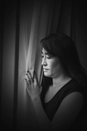 sadness and depress woman, absent minded, Staring out of the window in white tone