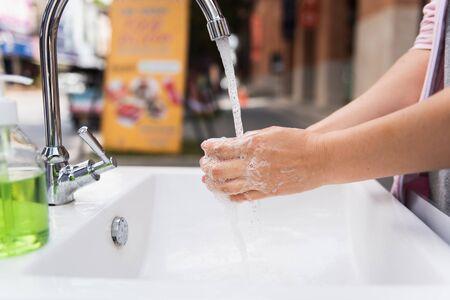 Corona virus travel prevention wash hands with soap in public walking street. Hand hygiene for coronavirus outbreak. Stock Photo