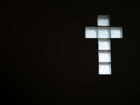 White glass block wall in shape of cross inside building view