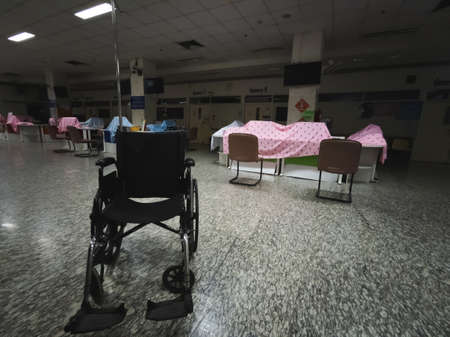 Chiangmai , Thailand on 12 June 2020 : wheelchair in hospital with empty people at night, out of service concept, prevent for coronavirus prevention COVID-19