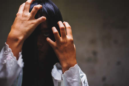 Horror shot, hand of woman cover her out face at old Abandoned building Banco de Imagens