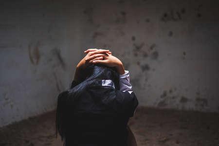 photo of children hand around head with lower head at dark corner, imprison, retarded, Child Abuse