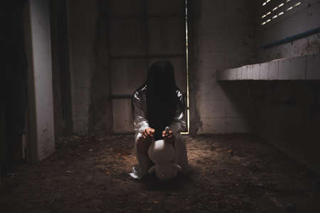 Mysterious Woman, Horror scene of scary ghost woman holding a doll at the dark corner of old Abandoned building