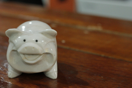 hand carved: Hand carved white onyx pig figurine on the wood back