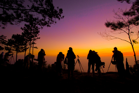 Silhouette of people taking a photo of sunrise at Phukradueng National Park of Thailand. Stock Photo