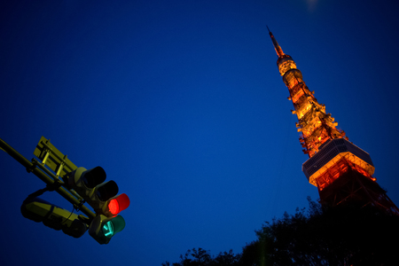 Tokyo Tower at twilight blue sky. Tokyo Tower is one of the symbol and landmark of Japan capital. View from the roadside with traffic lights.