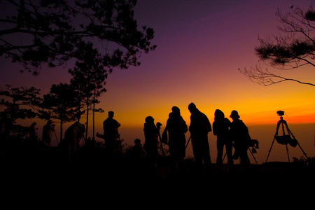 Phukradueng National Park of Thailand. Silhouette of people taking a photo of sunrise.