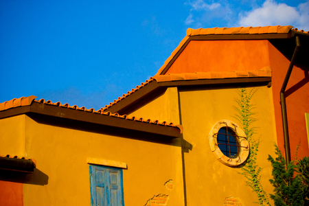 Close up colorful yelloworange house with blue sky.