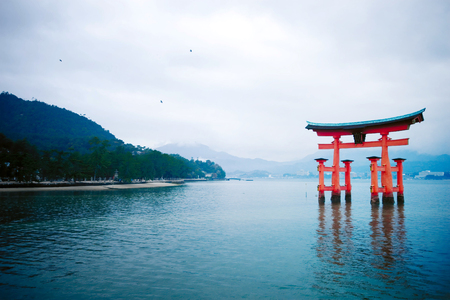 The great O-Torii of Itsukushima Shrine in the water with mountain of Miyajima island in the background - Hiroshima, Japan. Stock Photo