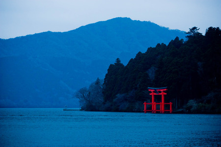 Japanese shrine Torii gate on the shore with the forest and mountain in background on Ashi lake at Hakone, Japan. Stock Photo