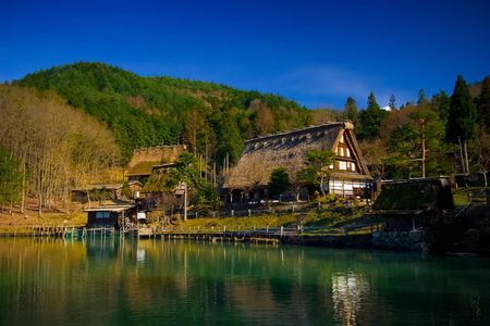 Hida Folk Village (Hida No Sato) with blue sky in spring season, Takayama, Japan. An open air museum with over 30 traditional houses from the Hida region, including Gassho-Zukuri style farmhouses.