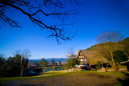 gassho zukuri: Hida Folk Village (Hida No Sato) with blue sky in spring season, Takayama, Japan. An open air museum with over 30 traditional houses from the Hida region, including Gassho-Zukuri style farmhouses.