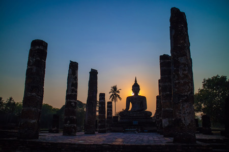 Silhouette of big buddha statue inside ruin temple at Sukhothai Historical Park, in Thailand.