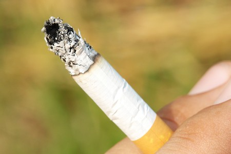 cigarette on hand with green and blur background Stock Photo - 5879186