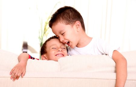 Two children on a sofa, smiling and playing photo