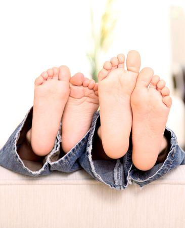 pie bebe: pies de dos ni�os mirando en un sof�. Imagen tierna y divertida