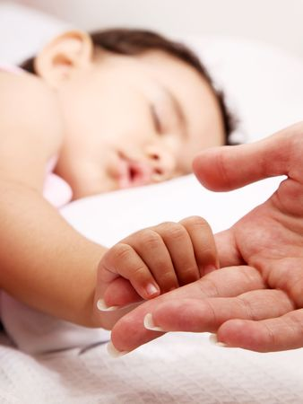 Baby sleeping take the hand of her mother photo