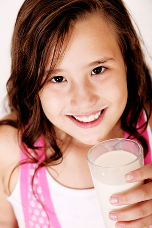Beautiful girl drinking milk in a glass and looking at the camera Stock Photo - 5879457