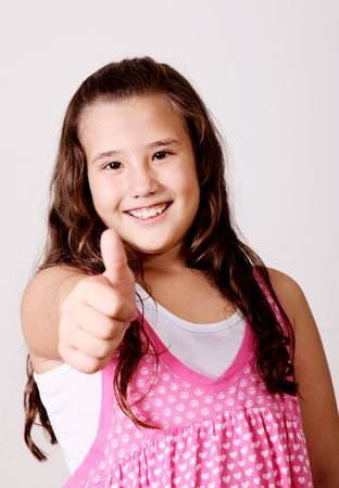 look right: 10 year old girl looking at the camera expressing a positive attitude with her hands