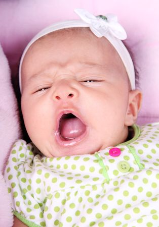 Face of beautiful baby yawning on a pink blanket  photo