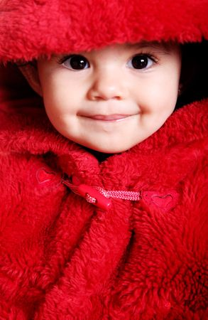 Closeup. Beautiful baby with red hood over white background photo