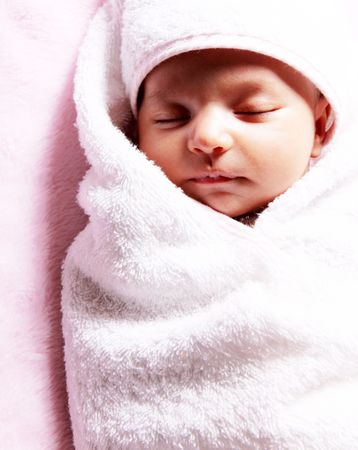 Beautiful baby wrapped in a white blanket photo